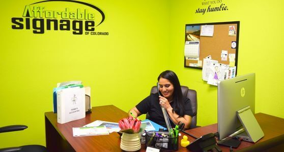 Employee takes call Affordable Signage Colorado